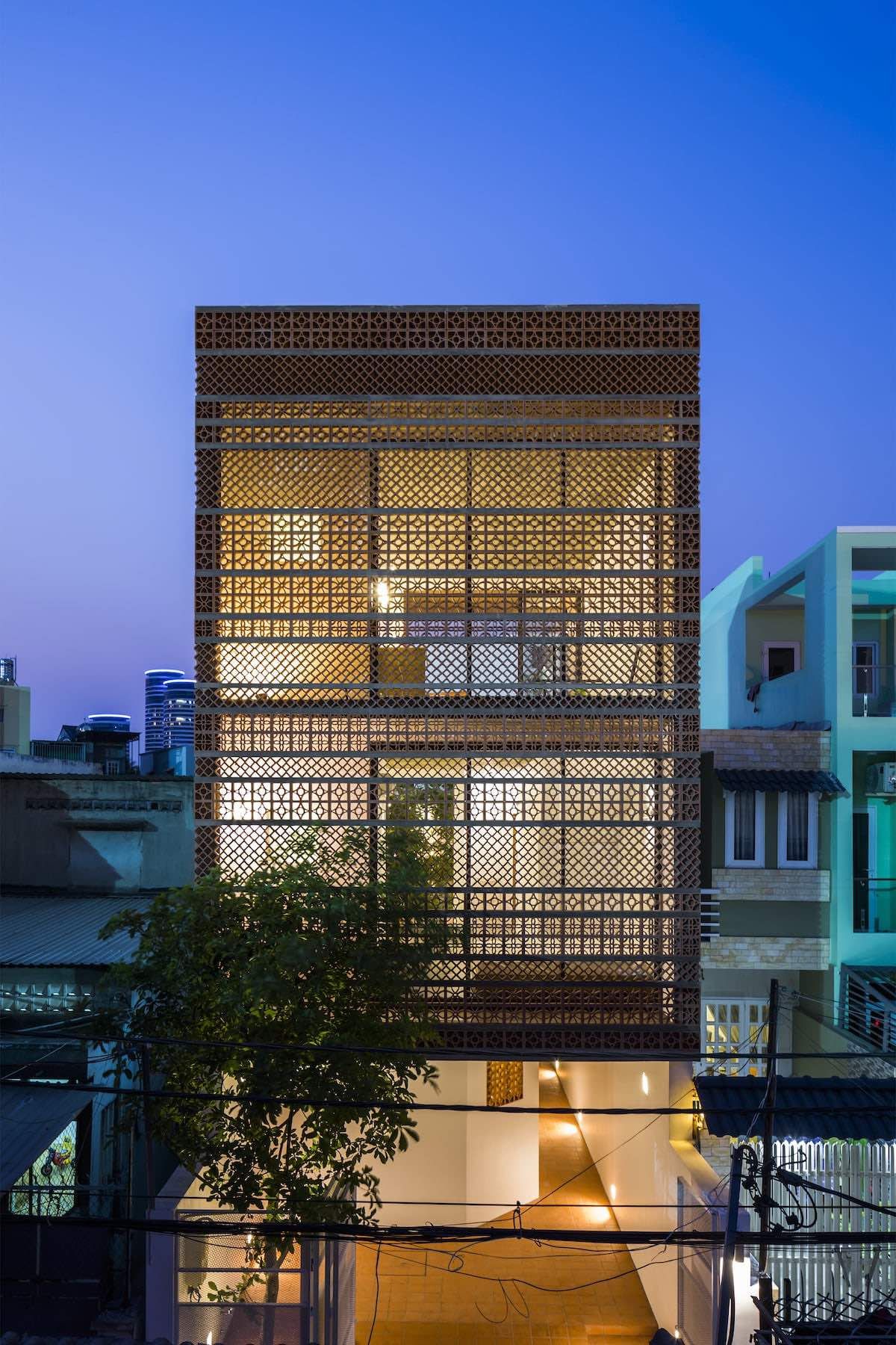 Exterior view of Binh Thanh Apartment at night // Design by SDA Architects // Image courtesy of Hiroyuki Oki